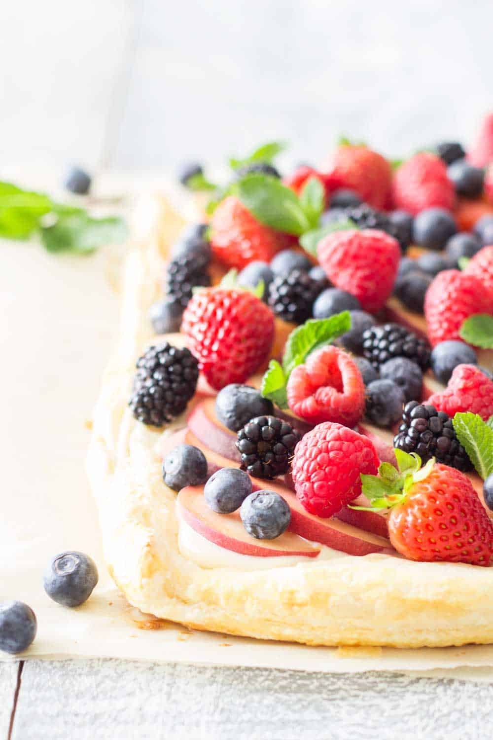To-die-for Summer Fruit Tart made with 15-Minute Puff Pastry, a layer of lime flavoured sweet cream cheese, sweet peaches and abundant fresh berries!