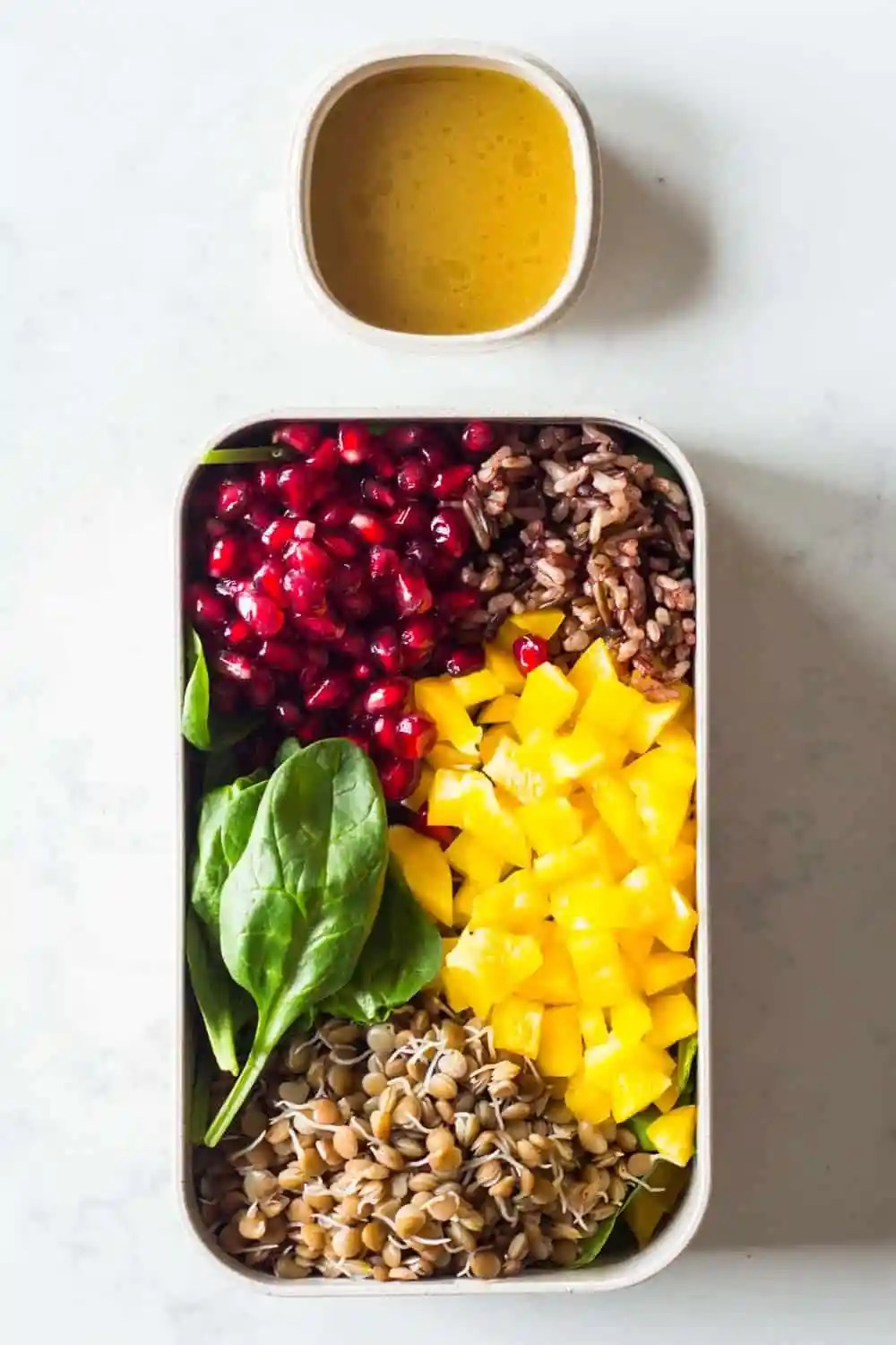Clean Eating Lunch for a Clean Eating Meal Plan - baby spinach, cooked sprouted lentils, cooked wild rice blend, pomegranate seeds, chopped bell pepper with a homemade honey-mustard salad dressing.