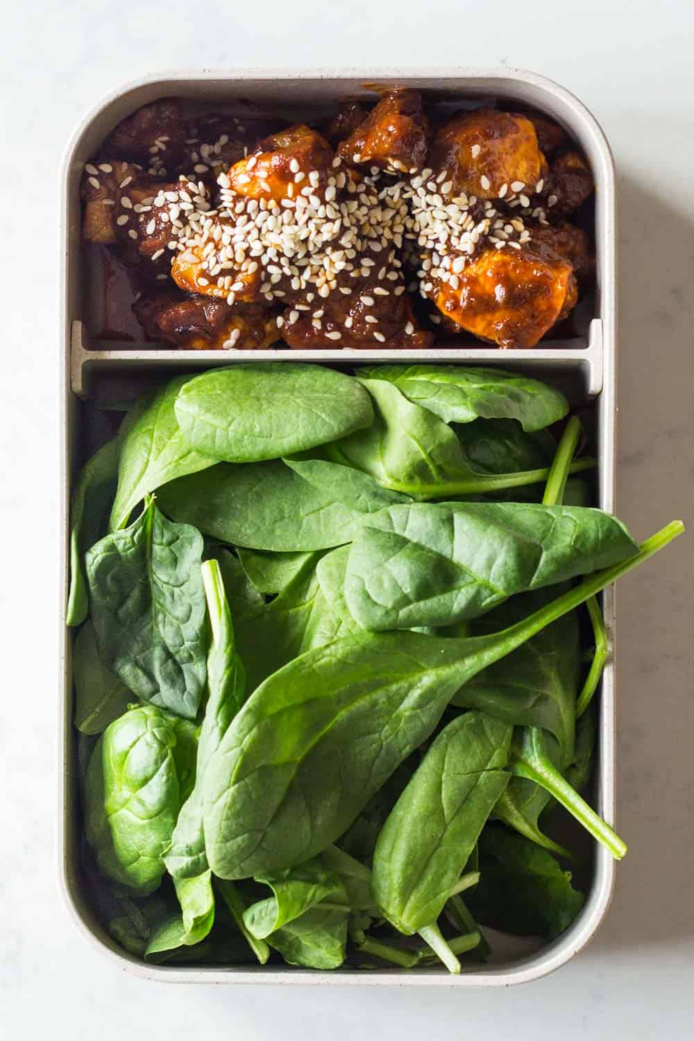 A healthy keto lunch for a complete keto diet plan - chicken curry made with coconut oil and full fat coconut milk, topped with sesame seeds and baby spinach on the side.