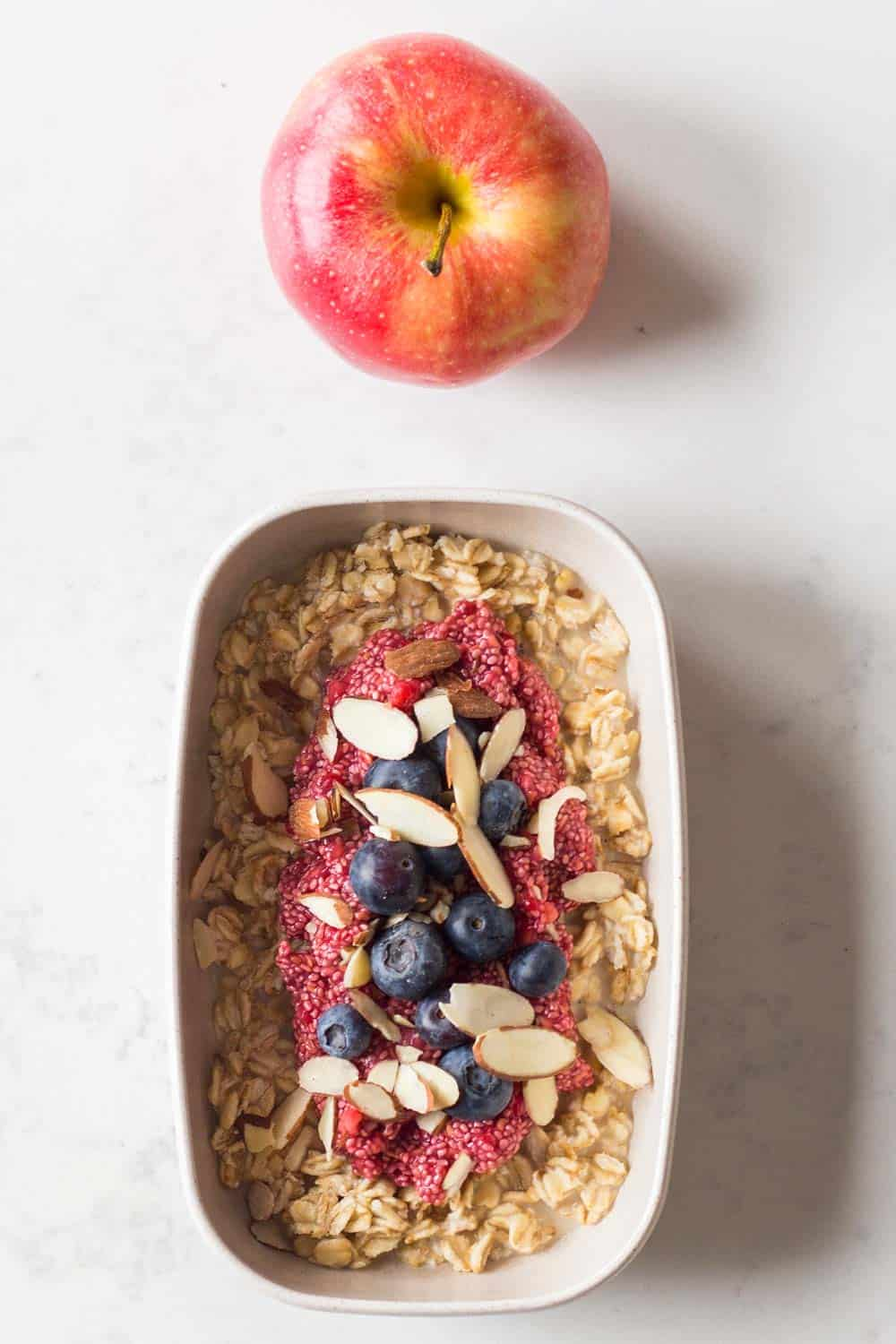 A Vegan Breakfast for a Nutritionally Balanced Vegan Meal Plan - maple-sweetened overnight oats made with almond milk, raspberry chia pudding, sliced almonds, blueberries and an apple.
