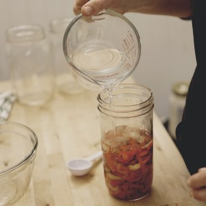 Making Pickled Peppers, pouring over the brin.
