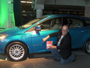 Green Living Guy with the book Build Your Own Electric Vehicle and the Ford Focus electric car