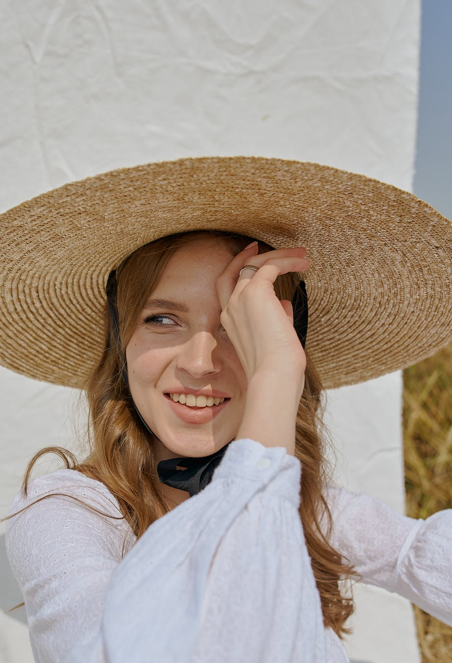 cheerful woman in hat standing near white sheet in countryside