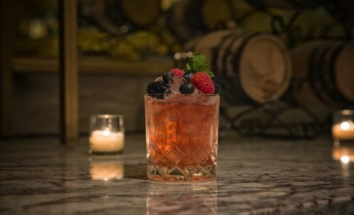 The Clumsy Workman cocktail featuring anejo rum, Tia Maria, berries and mint.