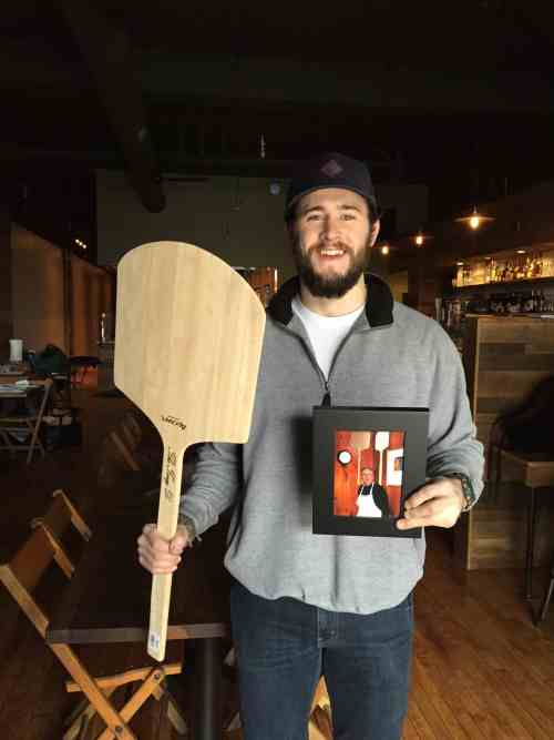 """TJ Gibs of Paulie Gee's Hampden with """"The Tony D"""" wooden peel"""