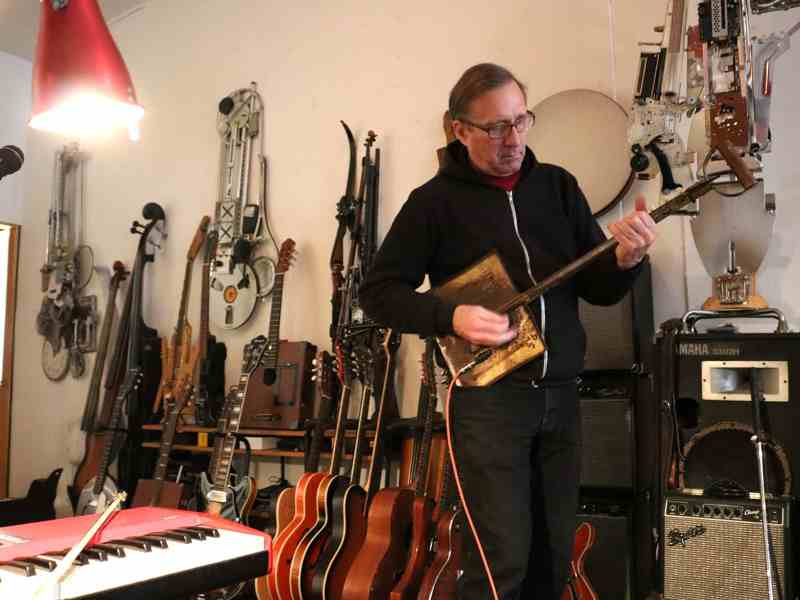 Ken Butler jamming on a shovel guitar in his studio. Photo: Megan Penmann