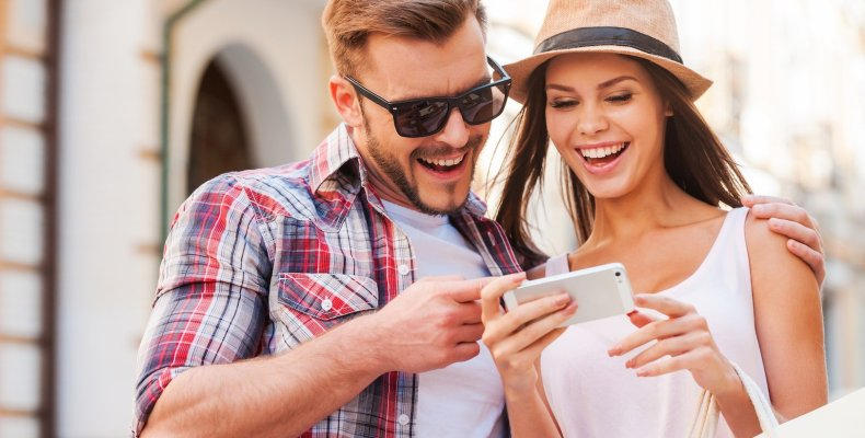 Couple Looking At Phone While Laughing