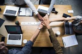 Business People Joining Hands Over Desk