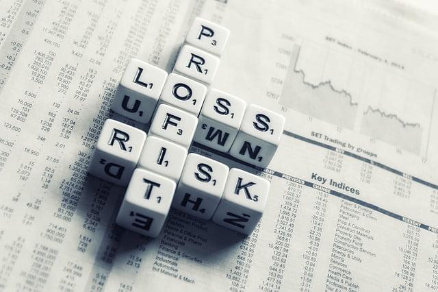 Profit Loss Risk Dice on Newspaper