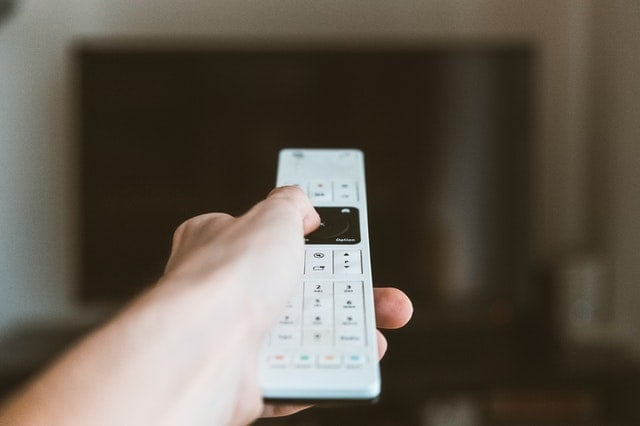 Hand Holding White Remote Control