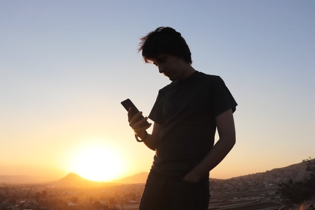 Man on Phone Silhouetted by Sunset