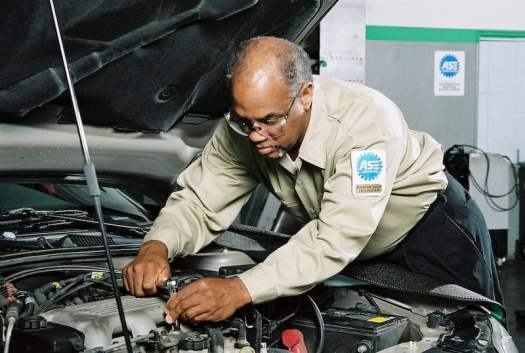 ASE Certified Mechanic Working on Engine
