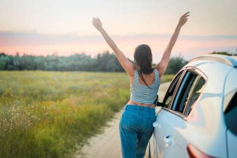 Woman With Arms Raised Next to Car