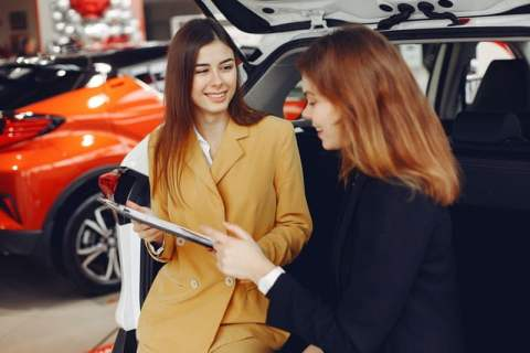 Two Women Discussing Car in Dealership