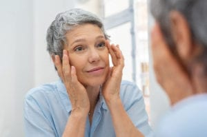 """Photograph of a middle-aged woman looking in the mirror and touching her wrinkles, from """"Health Benefits of Red Light Therapy: Legit or Hype?"""""""
