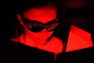 "Photograph of a young woman receiving red light therapy and wearing protective goggles, from ""The Health Benefits of Red Light Therapy: Legit or Hype?"""