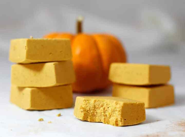 Bricks of pumpkin fudge on a table with a pumpkin behind them.
