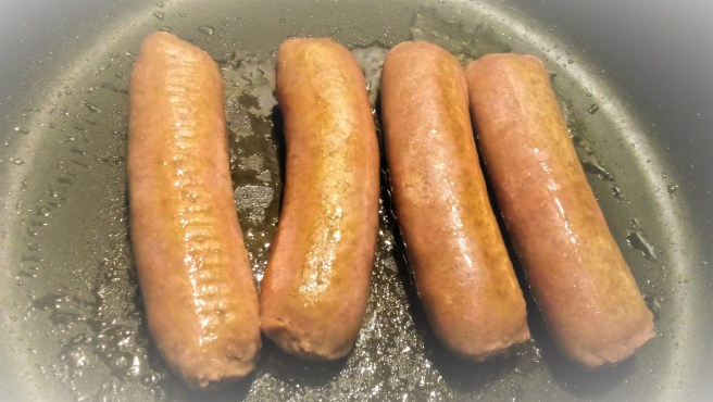 Four Beyond Meat plant-based sausages cooking in a nonstick pan.