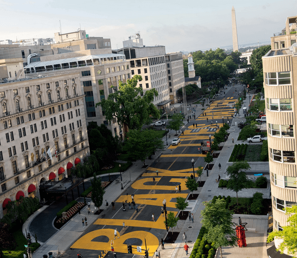 "Racial equality and ethical consumerism. A mural of the words 'Black Lives Matter"" painted in yellow on a road in Washington DC, 2 blocks from the White House, pointing to the Washington Monument."