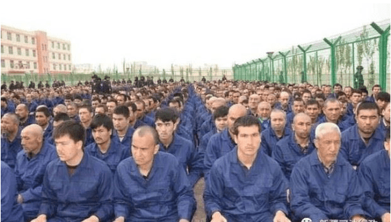 How to help the Uyghurs. Hundreds of men in matching blue jumpsuits sit on the ground between two barbed wire fences, surrounded by armed guards.