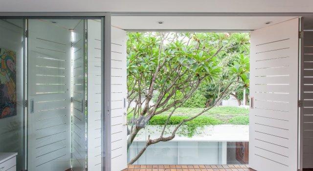As portas camarão de madeira ajudam no controle da radiação solar. Ao fundo, podemos ver o telhado verde. (Fonte: CR2 Arquitetura).