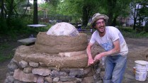 Josh Koppen using his natural building skills in constructing the cob oven