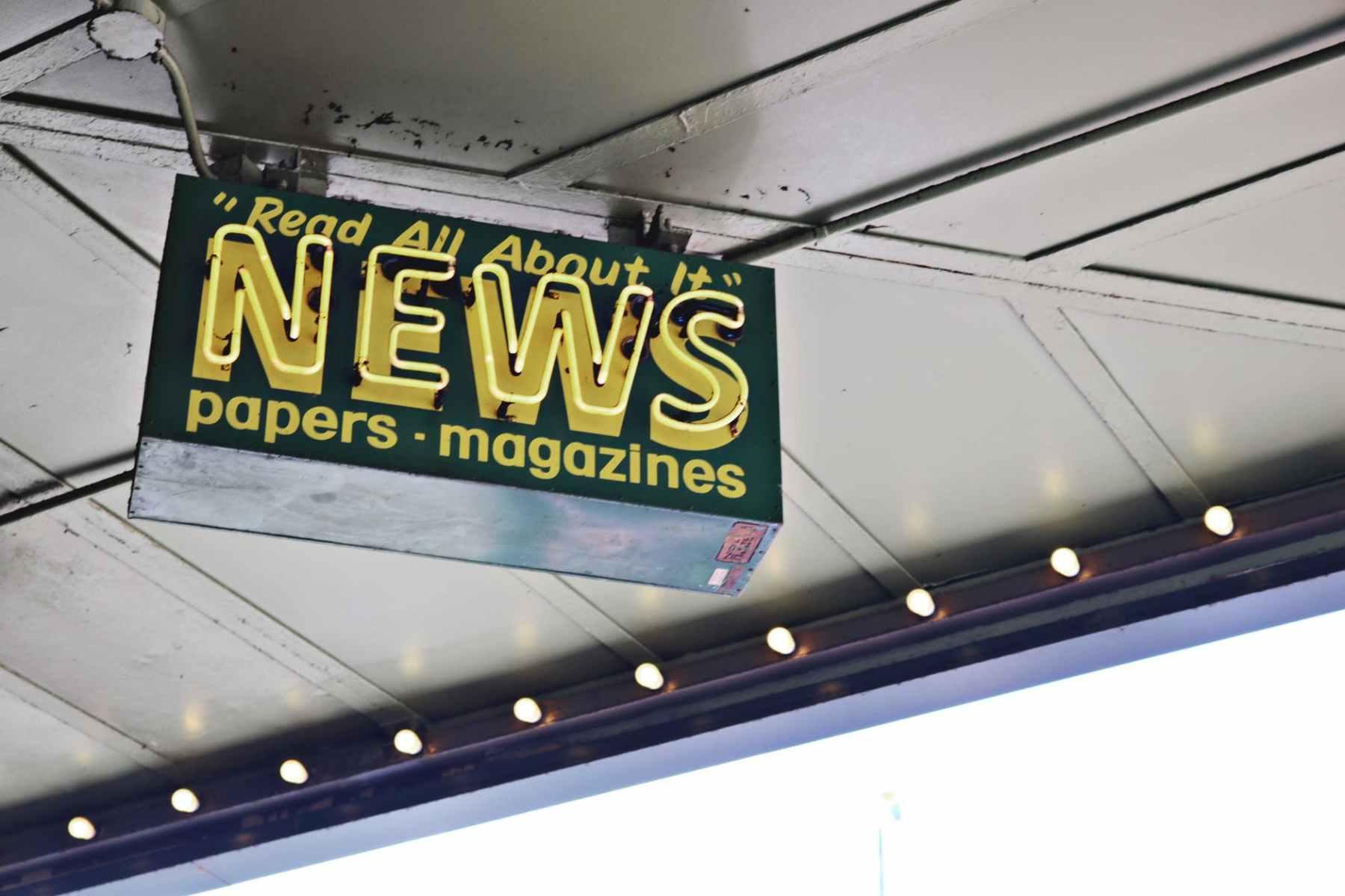 news inscription on neon signboard hanging on street