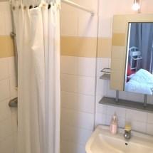 Das vollgeflieste Bad mit Dusche, WC und Waschbecken.