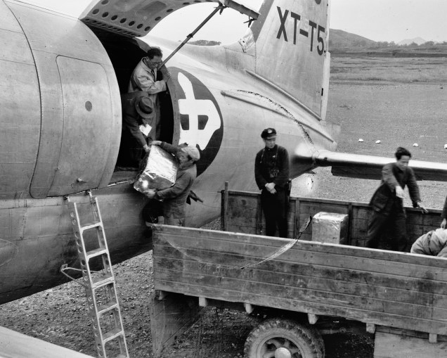 Unloading cargo from a C-46, late 1940s