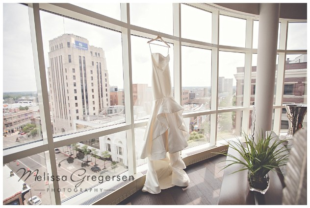 bridal gown hanging in the window of the Grand Loft Suite at the Radisson