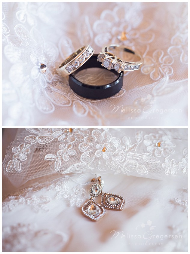 Wedding rings and the brides earrings perfectly placed on the wedding dress lace.
