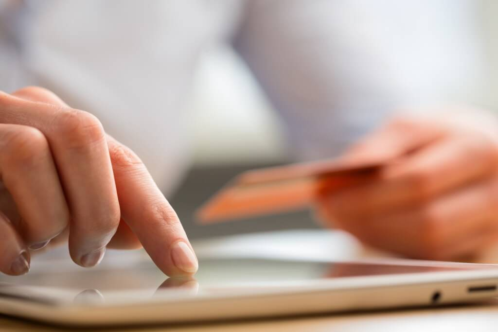 A young woman pays by credit card for e-commerce services through a tablet computer.