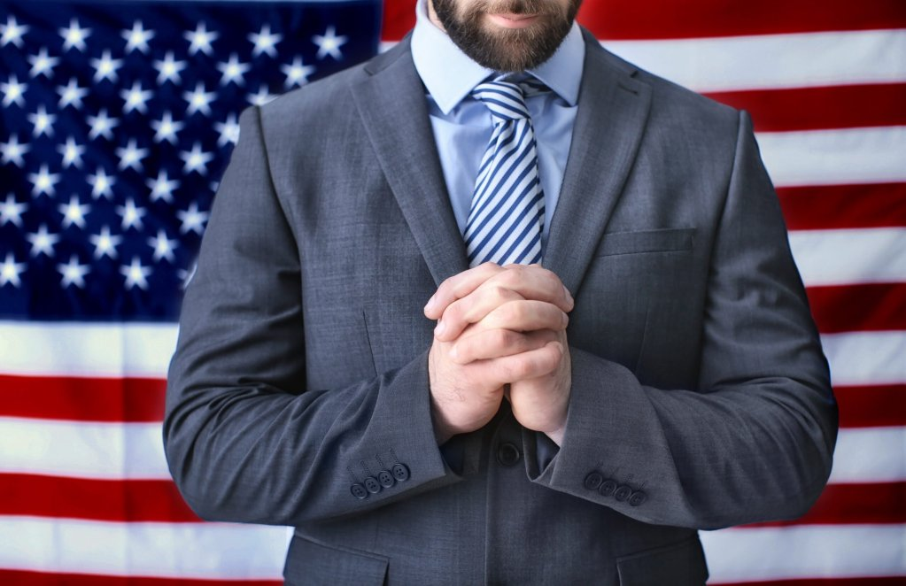 Image of professional looking man in suit praying in front of a flag - professional ministry kills Jesus