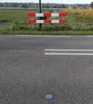 De grenspaal ín het asfalt
