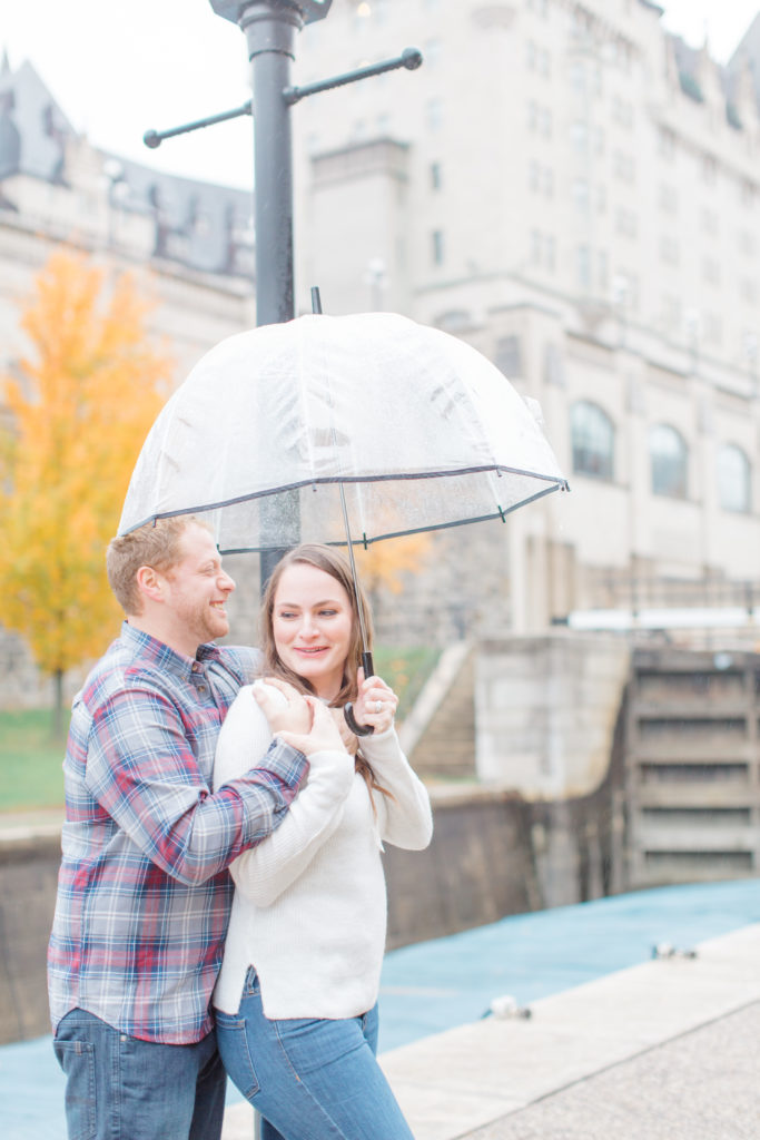 Couple standing in the rain during engagement session with the Locks and Chateau Laurier in the background having fun with each other