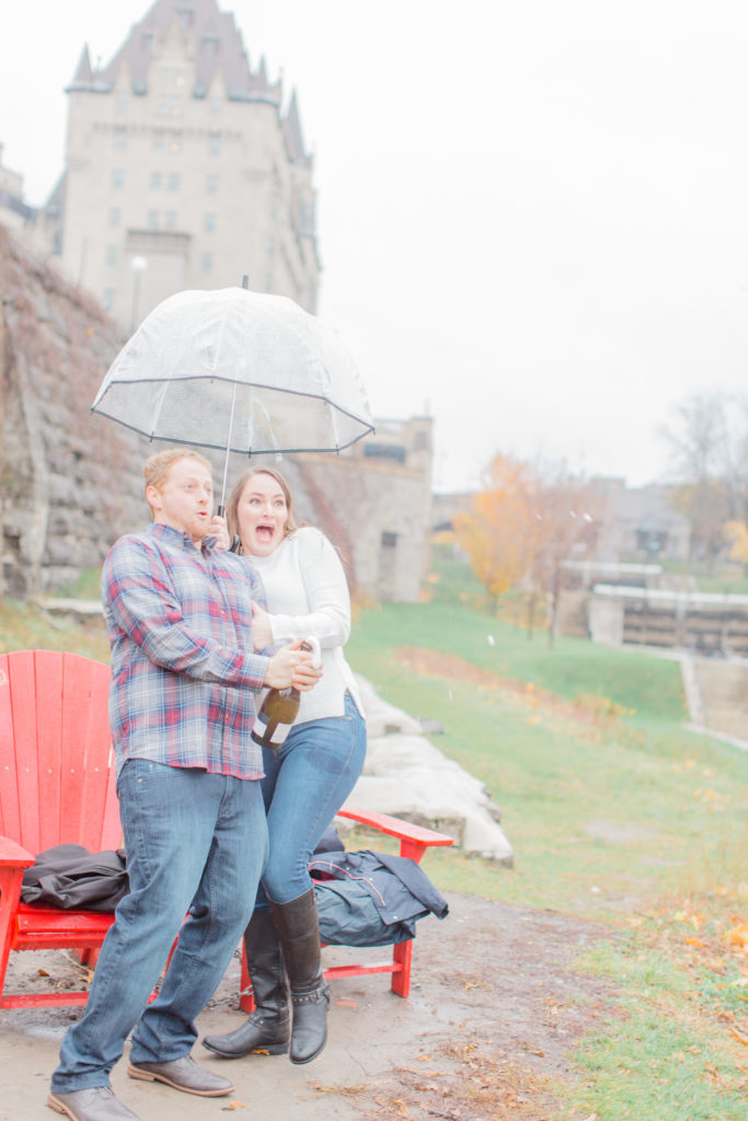 Couple standing in the rain during engagement session with the Chateau Laurier in the background popping bottle of champagne
