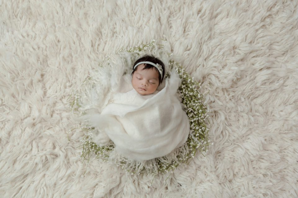 sweet baby girl wrapped in a white wreath newborn photo