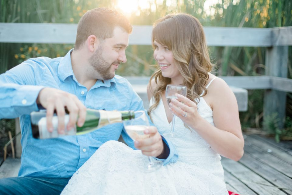 couple toasting champagne during an engagement session at mer bleue bog in ottawa east end wearing cute blue outfit with white dress