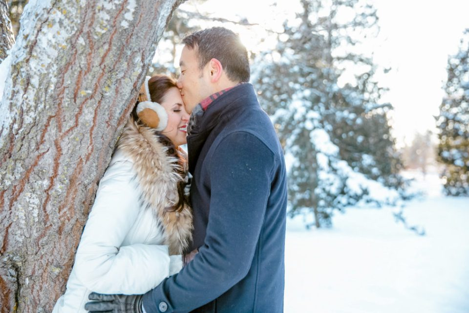 cute winter wonderland photo of couple during an engagement session in the dominion arboretum with cute accessories for winter