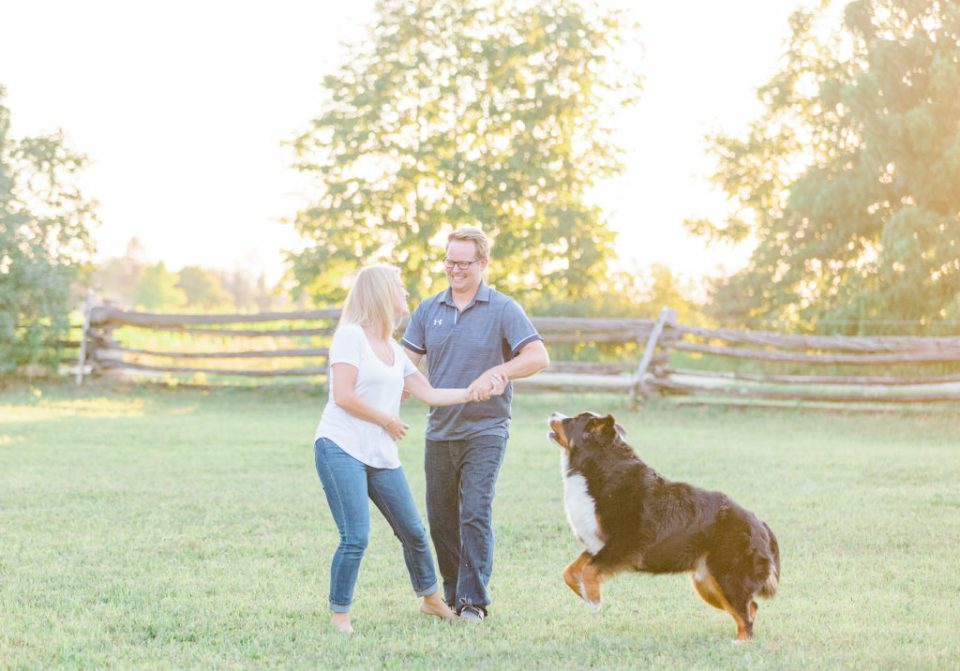 couple playing with dog during an engagement session in Carp