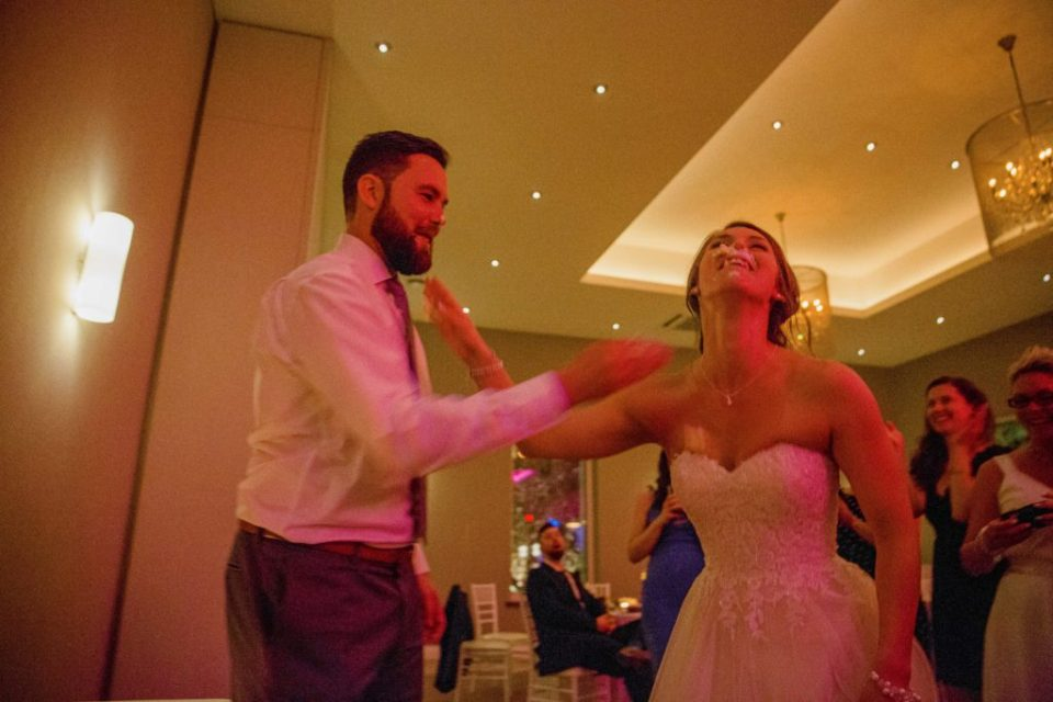 Bride and Groom smashing cake into each other's faces at a wedding during cake cutting - Classic -  Lavender Rain Inspired Wedding - Le Belvedere