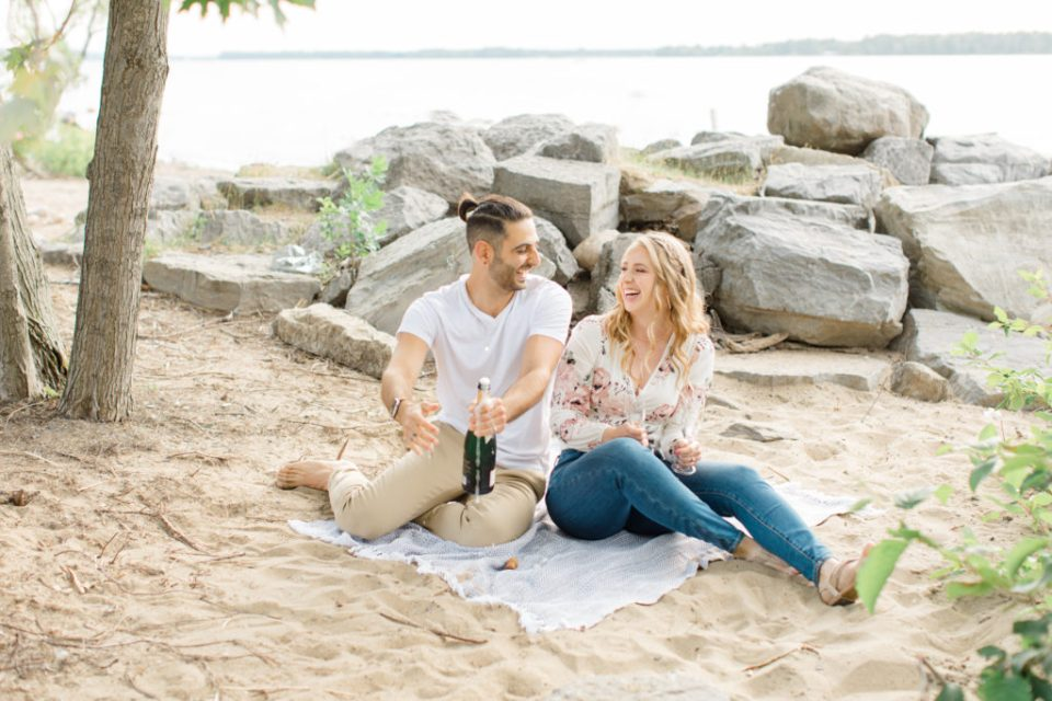 Laughing together - Sitting on the Beach - Ideas for what to wear for Engagement Photography, Modern Engagement Session Inspiration Wardrobe Ideas. Unsure of what to wear for your engagement photos, we've got you! Romantic floral shirt & jeans.  White T-shirt & neutral pants . Boat Shoes and Fancy. beaded sandals. Engagement at Petrie Island, Orleans. Grey Loft Studio is Ottawa's Wedding and Engagement Photographer Videographer for Real couples, showcasing photos that are modern, bright, and fun.