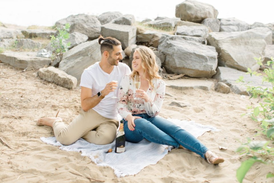 Cheers Shot - Sitting on the Beach - Ideas for what to wear for Engagement Photography, Modern Engagement Session Inspiration Wardrobe Ideas. Unsure of what to wear for your engagement photos, we've got you! Romantic floral shirt & jeans.  White T-shirt & neutral pants . Boat Shoes and Fancy. beaded sandals. Engagement at Petrie Island, Orleans. Grey Loft Studio is Ottawa's Wedding and Engagement Photographer Videographer for Real couples, showcasing photos that are modern, bright, and fun.