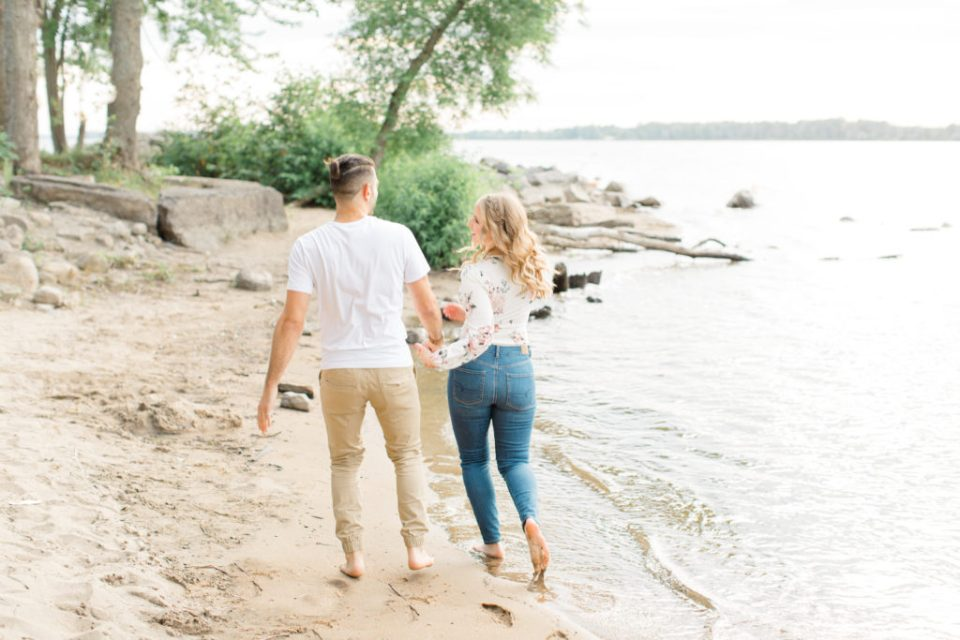 Walking on the Beach - Ideas for what to wear for Engagement Photography, Modern Engagement Session Inspiration Wardrobe Ideas. Unsure of what to wear for your engagement photos, we've got you! Romantic floral shirt & jeans.  White T-shirt & neutral pants . Boat Shoes and Fancy. beaded sandals. Engagement at Petrie Island, Orleans. Grey Loft Studio is Ottawa's Wedding and Engagement Photographer Videographer for Real couples, showcasing photos that are modern, bright, and fun.