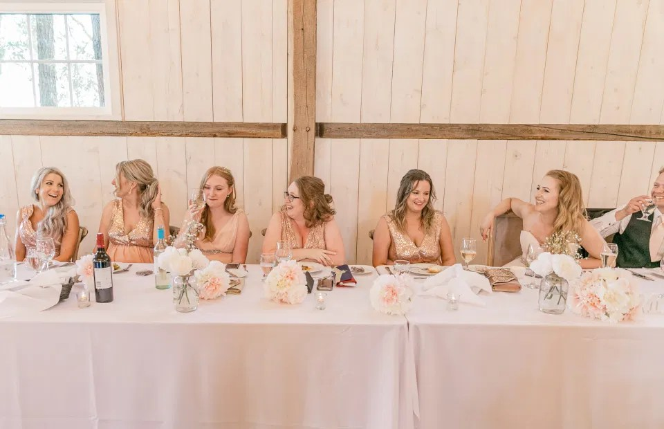 Bridal Party Head Table - Fun shots with Bridesmaids - Rose Gold Sequinned Dresses -  Stonefields Estate-  Bright and Airy - Natural Wedding Posing - Modern Wedding Blush &. Navy Wardrobe inspiration-  Romantic white with greenery, blush and navy theme. Grey Loft Studio is Stonefields Wedding and Engagement Photographer for Real couples, showcasing photos that are modern, bright, and fun.