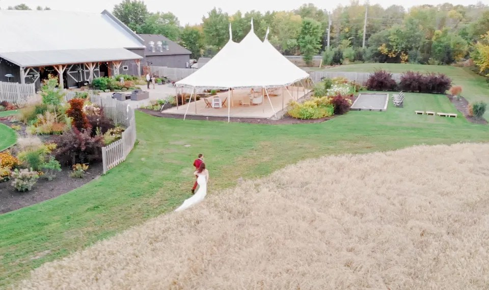 Arial Shot - Bride and Groom Posing in Field of Wheat - Ruby, Off-White, Silver, Greenery. Eucalyptus Leaves. An inspiration filled with soft neutrals, lush florals, and layers of romantic textures all set at Evermore Weddings and Events, Almonte Ontario.  Grey Loft Studio shot with Canon 5D Mark 4. Ottawa Wedding Photographer & Videographer Team.