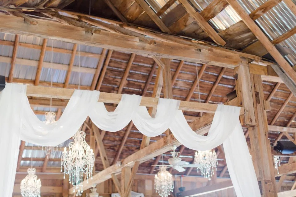 Hanging White Drapery in Evermore. Indoor Heritage Barn at Evermore Wedding's and Events - Almonte - Hanging Chandeliers, Rustic Modern Chairs, White linens. Ruby Red Lovely Wedding at Evermore.