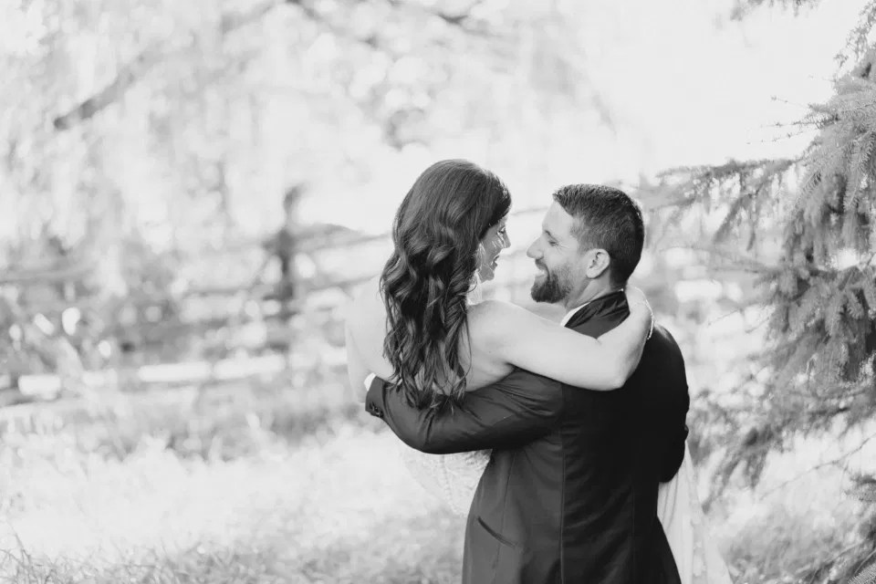 Lifting his Bride - Black and White -  Bride and Groom - Standing in a Field - Off-White, Silver, Greenery. Eucalyptus Leaves. An inspiration filled with soft neutrals, lush florals, and layers of romantic textures all set at Evermore Weddings and Events, Almonte Ontario.