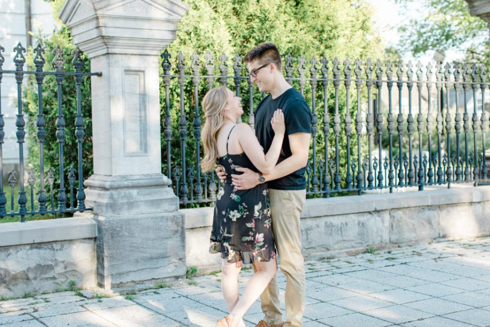Standing at Rideau Hall - Ideas for what to wear for Engagement Photography, Modern Engagement Session Inspiration Wardrobe Ideas. Unsure of what to wear for your engagement photos, we've got you! Romantic floral dress. Black Polo T-shirt & neutral pants . Boat Shoes and Fancy beaded wedges. Engagement downtown Ottawa. Grey Loft Studio is Ottawa's Wedding and Engagement Photographer Videographer for Real couples, showcasing photos that are modern, bright, and fun.