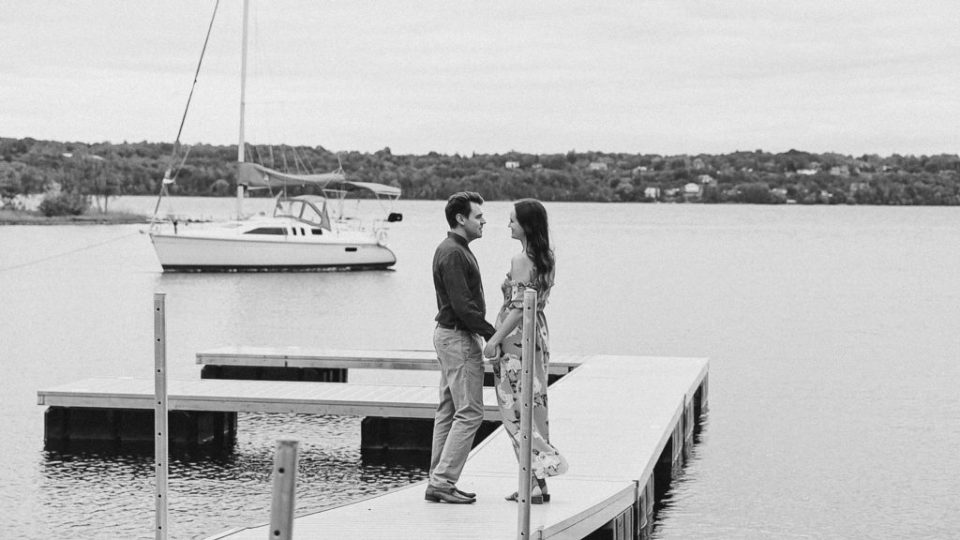 Standing on Dock - Couple- in Black and White-Ideas for what to wear for Engagement Photography, Modern Engagement Session Inspiration Wardrobe Ideas. Unsure of what to wear for your engagement photos, we've got you! Romantic white with Pink Flower dress for Summer Engagement in Ottawa. Grey Loft Studio is Ottawa's Wedding and Engagement Photographer for Real couples, showcasing photos that are modern, bright, and fun.